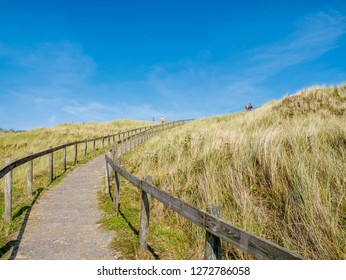 AMELAND, NETHERLANDS - AUG 27, 2017: Footpath between wooden fences leading up to viewpoint dune with people in nature reserve Het Oerd on West Frisian island Ameland, Friesland