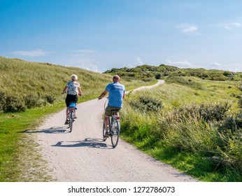 AMELAND, NETHERLANDS - AUG 27, 2017: Rear view of people riding bicycles on bicycle path in dunes of nature reserve Het Oerd on West Frisian island Ameland, Friesland, Netherlands