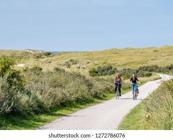 AMELAND, NETHERLANDS - AUG 27, 2017: People riding bicycles on bicycle path in dunes of nature reserve Het Oerd on West Frisian island Ameland, Friesland, Netherlands