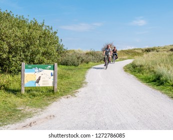AMELAND, NETHERLANDS - AUG 27, 2017: People riding bicycles and information board in dunes of nature reserve Het Oerd on West Frisian island Ameland, Friesland, Netherlands