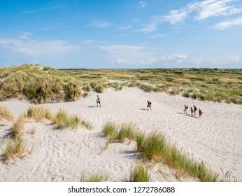 AMELAND, NETHERLANDS - AUG 27, 2017: Panorama of dune landscape with people walking in nature reserve Het Oerd on West Frisian island Ameland, Friesland, Netherlands