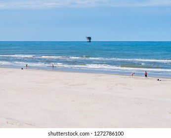 AMELAND, NETHERLANDS - AUG 27, 2017: People playing on beach and North Sea with offshore drilling platform, West Frisian island Ameland, Friesland, Netherlands