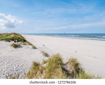 AMELAND, NETHERLANDS - AUG 27, 2017: People sitting together on sand dune looking over beach and North Sea on West Frisian island Ameland, Friesland, Netherlands