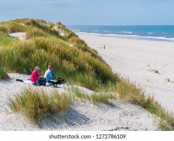 AMELAND, NETHERLANDS - AUG 27, 2017: People having picnic on sand dune looking over beach and North Sea on West Frisian island Ameland, Friesland, Netherlands
