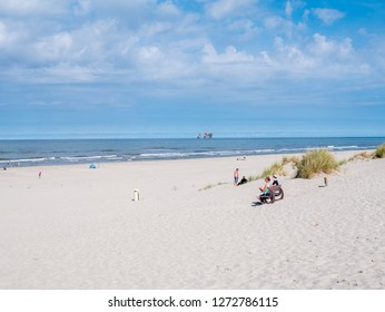 AMELAND, NETHERLANDS - AUG 27, 2017: People on beach and North Sea with offshore drilling platform, West Frisian island Ameland, Friesland, Netherlands