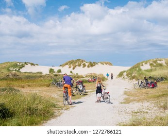 AMELAND, NETHERLANDS - AUG 27, 2017: People with bicycles in dunes in nature reserve Het Oerd on West Frisian island Ameland, Friesland, Netherlands