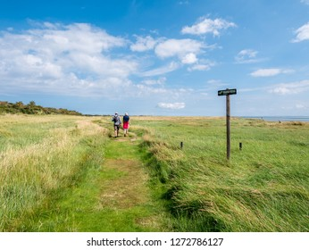 AMELAND, NETHERLANDS - AUG 27, 2017: People walking on footpath and no access sign in nature reserve Het Oerd at Wadden Sea coast of West Frisian island Ameland, Friesland, Netherlands