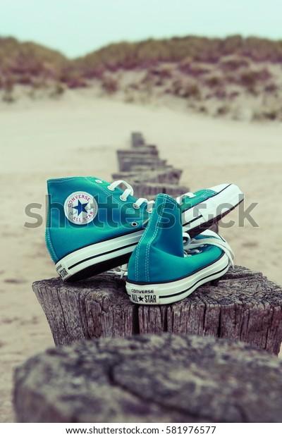 AMELAND, NETHERLANDS - SEPTEMBER 13, 2014: All Star Converse sneakers on beach.
