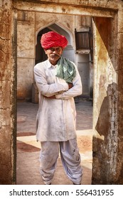 AMER, INDIA - NOVEMBER 18, 2016: An anonymous worker in traditional attire of a white uniform and red turban is framed by a doorway in the Man Singh Palace of the Amber Fort near Jaipur, India.