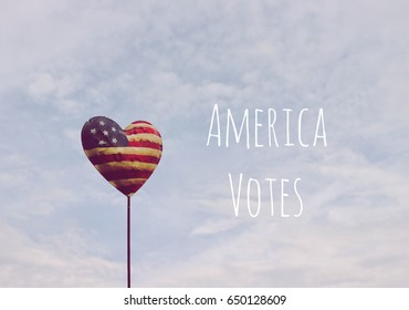 America votes sign, American flag heart on sky