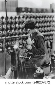 America WW1 woman arsenal worker. 1918. She is welding a water jacket for a machine gun. Thewaterjacket keeps the guns from overheating.