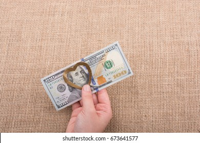 American 100 dollar banknotes with a heart clip in hand