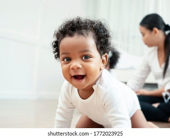 The American Afican boy is crawling and smiling for the camera.