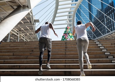 American and African black friends run upstair of skywalk with modern building background. Bodybuilding and healthy lfiestyle. New normal for sport exercise with social distancing to prevent covid-19.