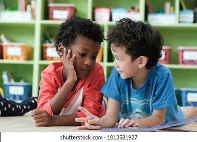American and African boys are reading together with happiness in their kindergarten classroom, kid education and diversity concept