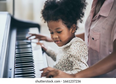American African young pianist, teacher teaching girl kid student to play piano, Art of music education concept