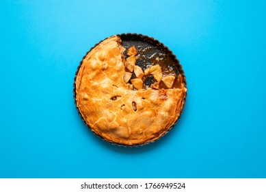 American apple pie with golden crust in a tray on blue background. Apple tart with caramel sauce. Homemade Thanksgiving dessert. Autumn sweet food.