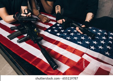 American arms dealers with weapon. Unrecognizable people with tattoos hold guns and rifles in their hands. Outlaw, ghetto, murderer, armed attack concept