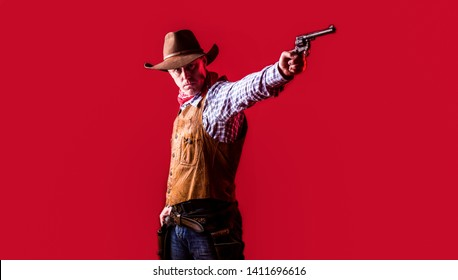 American bandit in mask, western man with hat. Portrait of farmer or cowboy in hat. Man wearing cowboy hat, gun. West, guns. Portrait of a cowboy. owboy with weapon on red background.