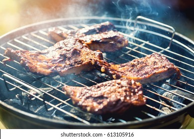american barbecue - preparing beef ribs on charcoal grill