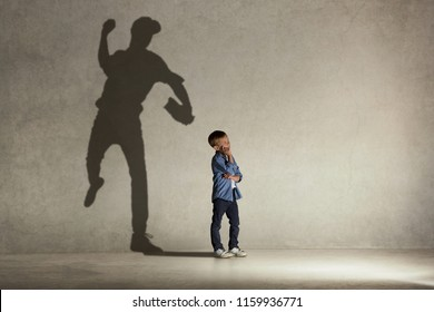 American baseball champion. Childhood and dream concept. Conceptual image with boy and shadow of fit athlete on the studio wall