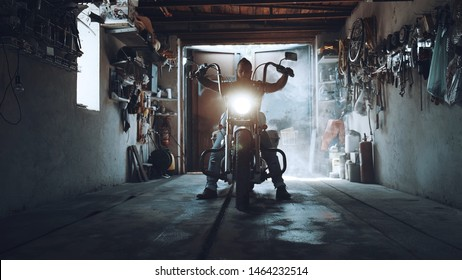 American biker with his motorcycle in the garage. cool and powerful chopper which the biker collected with his own hands