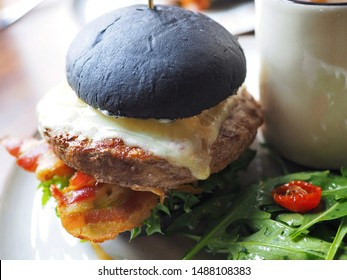 American black charcoal burger with oversized Wagyu beef patties topped with cheese, crispy bacon, fresh vegetables with rocket salad as along side dish on wooden table with sun light reflection