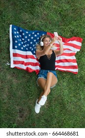 American blonde woman resting on the grass with the American flag listening to her playlist with her wireless headphones