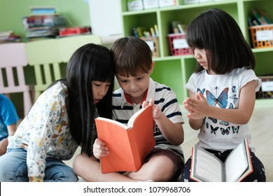 American boy and asian girl are reading together with happiness in their kindergarten classroom, kid education and diversity concept
