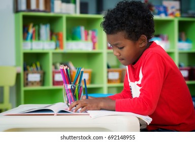 American boy make home wore and drawing in preschool library, education, kid, and school concept