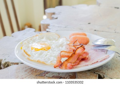 american breakfast with fried egg,bacon,sausage and ham.on wood table.selective focus.