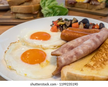 American breakfast with fried eggs, sausages, ham, toasted bread and vegetables. Easy, fast cooking food in rush hour. Most popular breakfast always serve in the morning around the world.