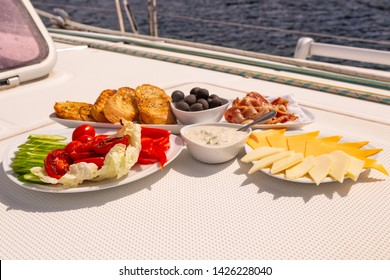 American breakfast on sailing yacht. Luxury holiday meal at the sea on the yacht. Bacon, omelette, eggs, toasts, olives, cheese, BBQ, tomato, cucumber, Tzatziki, cacık, tarator, salad, garlic