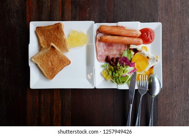 American Breakfast style, pork sausage, ham, fried egg with salad and toast in white plate on wooden table.