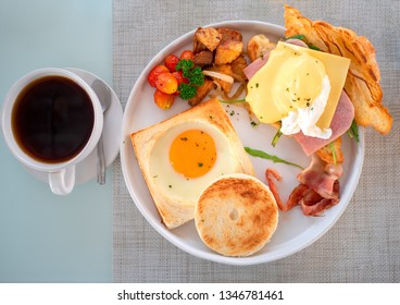American breakfast with sunny side up eggs, bacon, toast, bread, croissant and coffee on table
