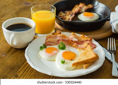 American breakfast with sunny side up eggs, bacon, toast, pancakes, coffee and juice, wood background