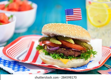 American Burger with cheese,tomato,pickle,red onion,lettuce and Lemonade at a Picnic for 4th of July