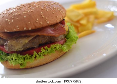 American burger with fried potatoes on a white plate.