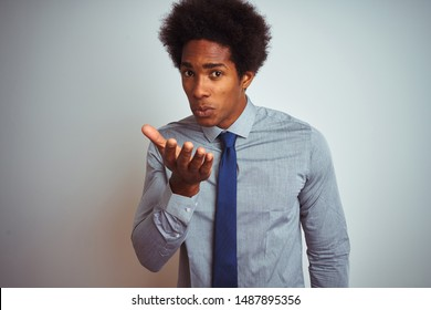 American business man with afro hair wearing shirt and tie over isolated white background looking at the camera blowing a kiss with hand on air being lovely and sexy. Love expression.