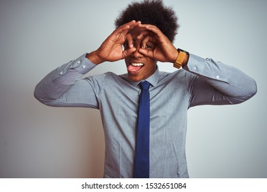 American business man with afro hair wearing shirt and tie over isolated white background doing ok gesture like binoculars sticking tongue out, eyes looking through fingers. Crazy expression.
