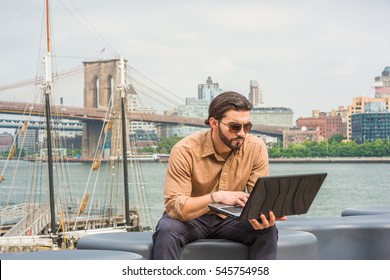 American Business Man travels, works in New York, wearing brown shirt, sunglasses, sits by river, hunching back, reading on laptop computer. Brooklyn bridge, boat on background.