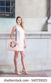 American Business Woman Fashion in New York, wearing sleeveless antique white dress with doll collar, high heels, shoulder carrying bag, standing by vintage wall on street. Color filtered effect