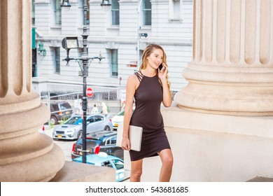 American Business Woman traveling, working in New York, wearing black dress, carrying laptop computer, talking on phone, walking up on stairs into office building from street. Color filtered effect