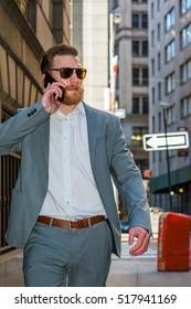 American businessman with beard, mustache traveling, working in New York, wearing cadet blue suit, white undershirt, sunglasses, walking through crowded high building street, talking on cell phone.