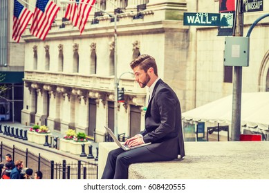 American Businessman with beard traveling, working in New York, wearing black suit, sitting on Wall Street outside vintage office building, looking down, working on laptop computer. Filtered effect
