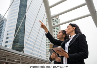 American Businesswoman boss discuss business project plan with her underling officer. Check develop progress via digital tablet and point finger to modern building.