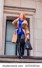 American businesswoman traveling, working in New York, wearing long brown woolen overcoat, blue undershirt, black pants, long leather boots, holding hand bag, walking down stairs, looking up, smiling.