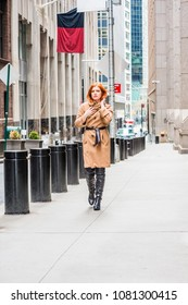 American businesswoman traveling, working in New York, wearing long brown woolen overcoat, black leather boots, hands touching coat, hair, walking on narrow vintage street in cold winter day.