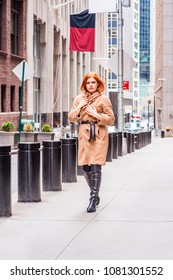 American businesswoman traveling, working in New York, wearing long brown woolen overcoat, black leather boots, hands touching coat, walking on narrow vintage street in cold winter day.