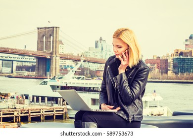 American Businesswoman traveling, working in New York, sitting by East River, working on laptop computer, talking on cell phone in same time. Brooklyn Bridge, boat on background. Filtered effect.
